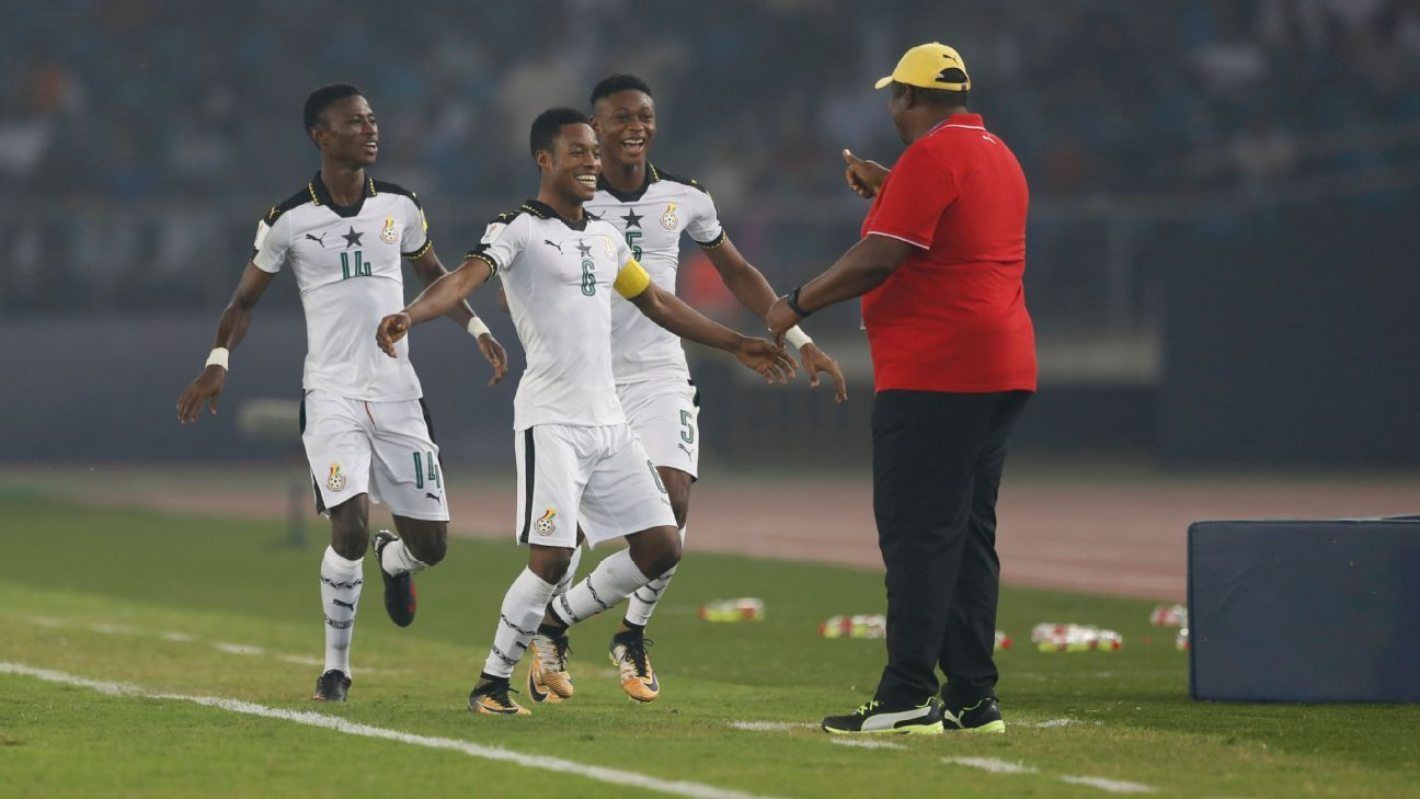 Ghana's Eric Ayiah (No. 6) celebrates a goal with his coach during the match against India in New Delhi.