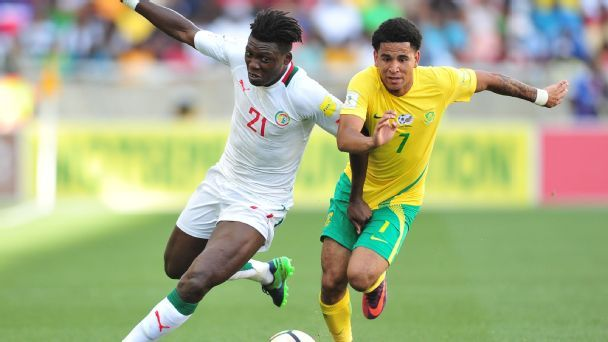 Keagan Dolly of South Africa challenged by Lamine Gassama of Senegal during their 2018 World Cup Qualifiers match at Peter Mokaba Stadium.