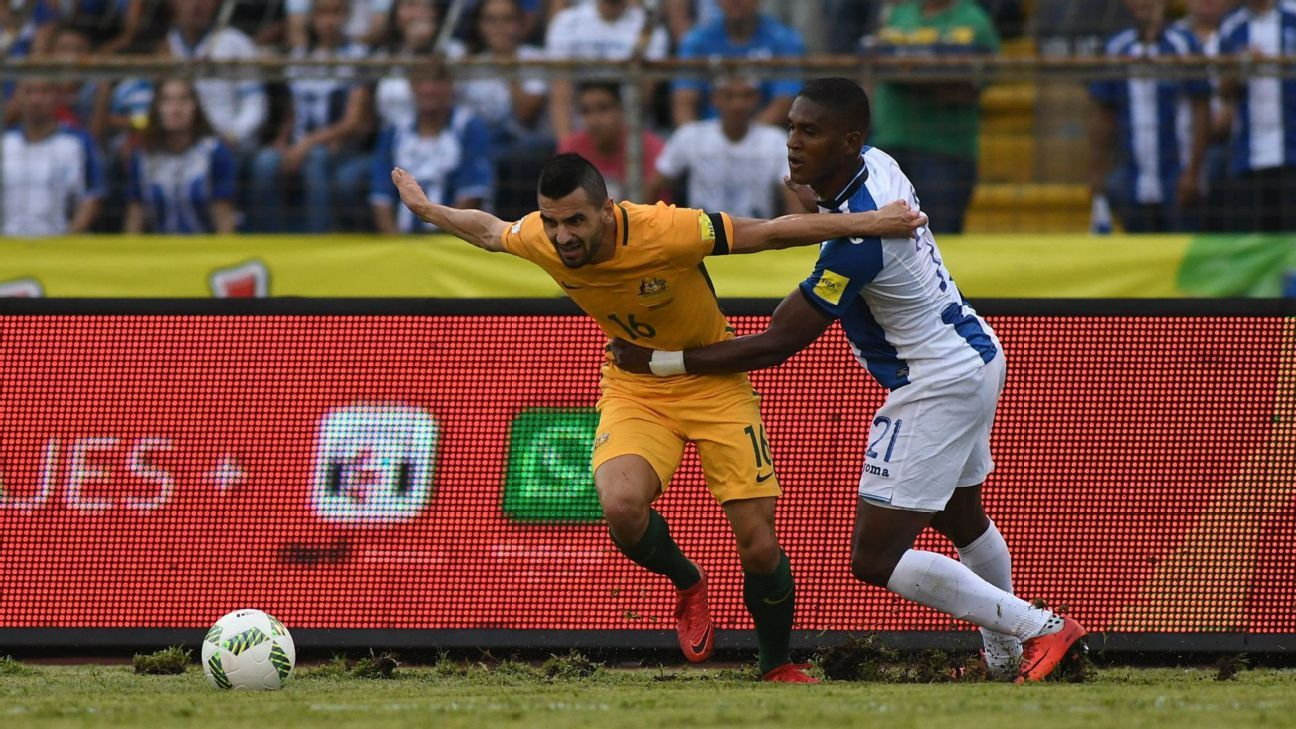 Australia's Aziz Behich, left, is grabbed by Honduras' Brayan Beckeles in their World Cup playoff on Friday.