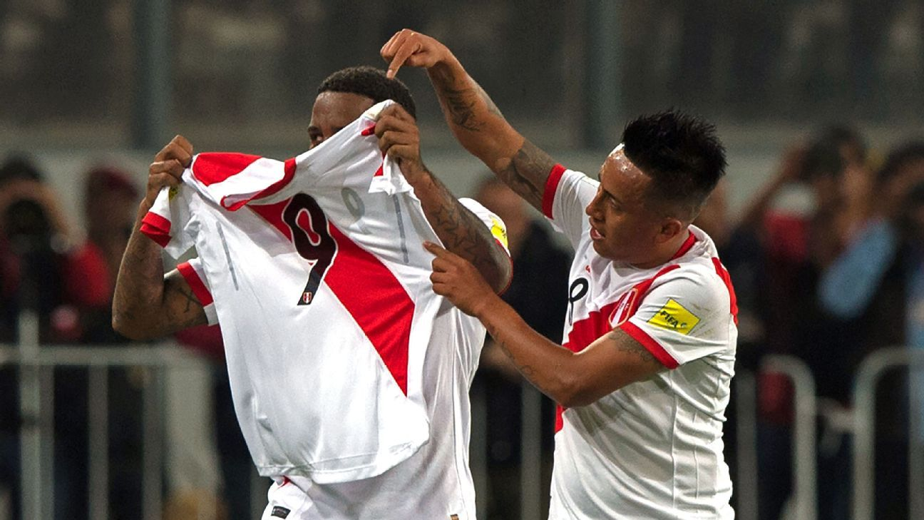 Christian Cueva, right, and Jefferson Farfan hold up the Peru jersey of suspended teammate Paolo Guerrero after scoring a goal.