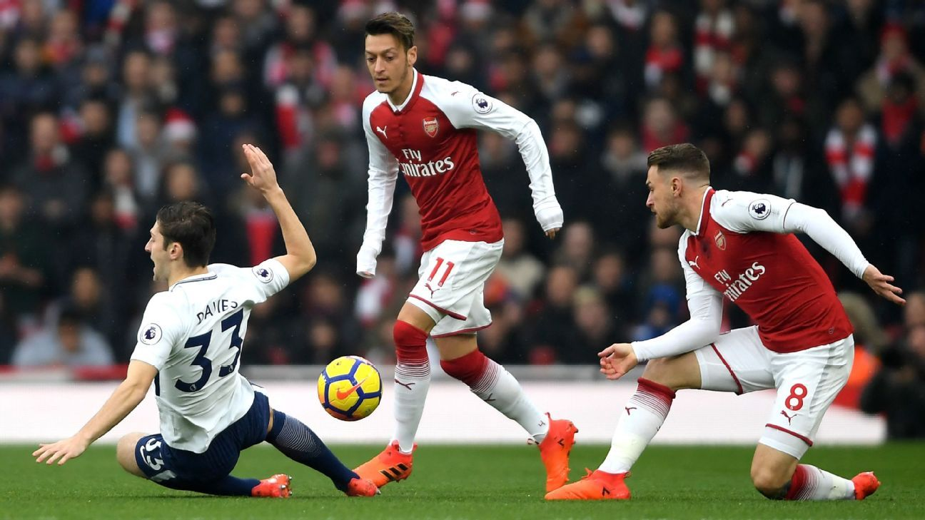Arsenal's Mesut Ozil and Aaron Ramsey battle with Ben Davies during the North London derby.