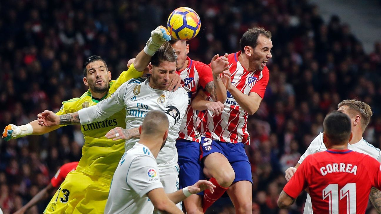 Jan Oblak and Sergio Ramos challenge for the ball during Atletico Madrid's La Liga fixture with Real Madrid.