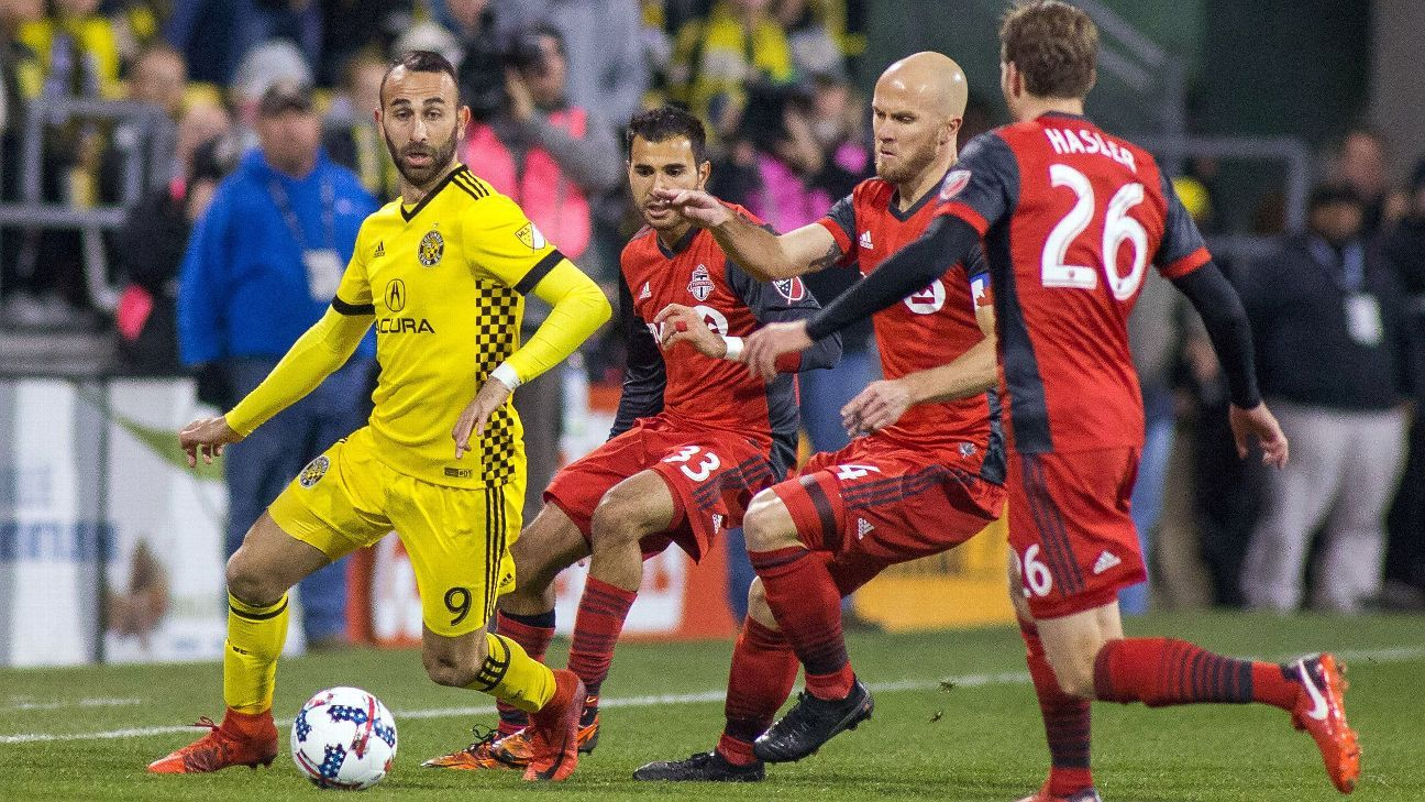 Justin Meram battles three defenders during Columbus' MLS playoff against Toronto.