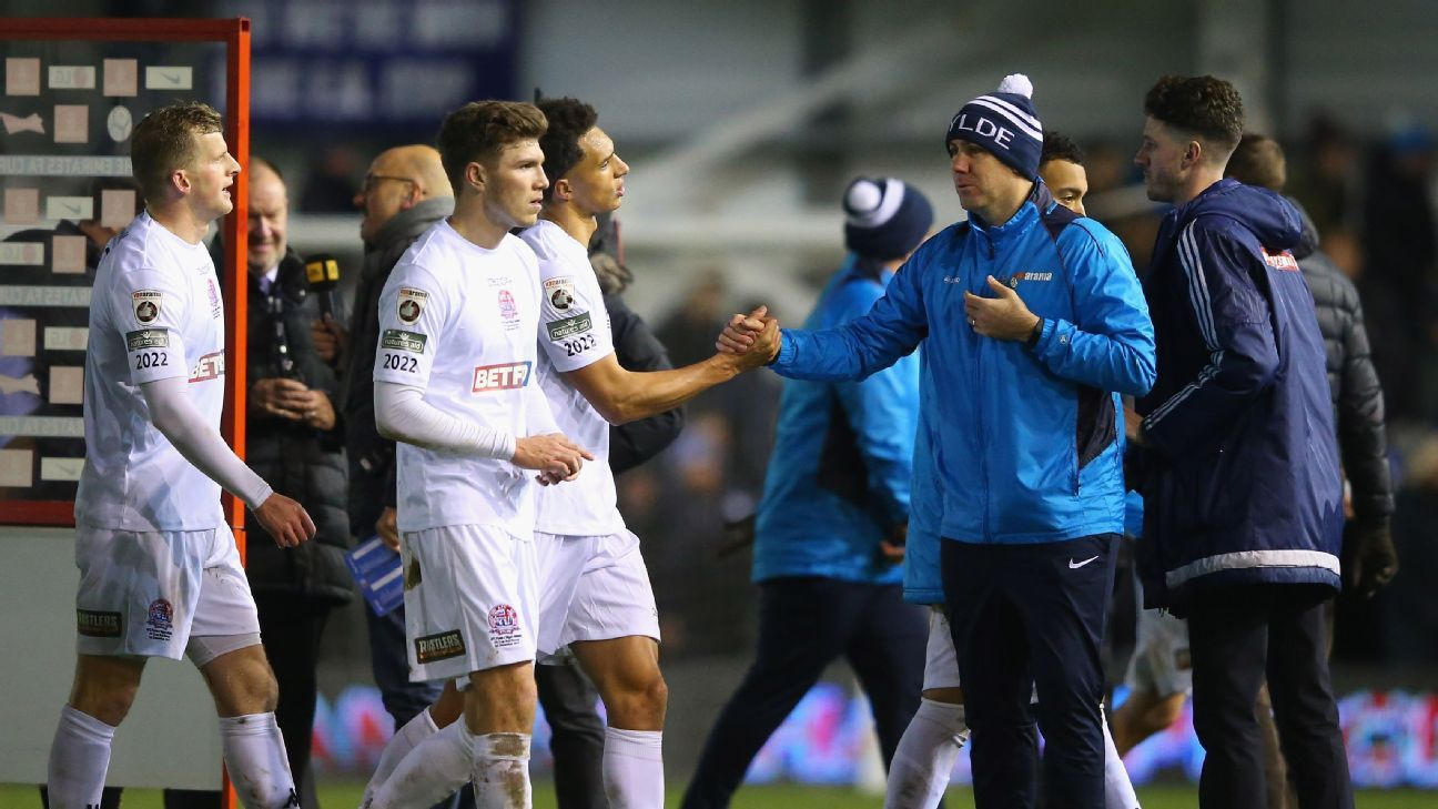 Dave Challinor the manager of AFC Fylde congratulates his players after an FA Cup draw with Wigan Athletic.