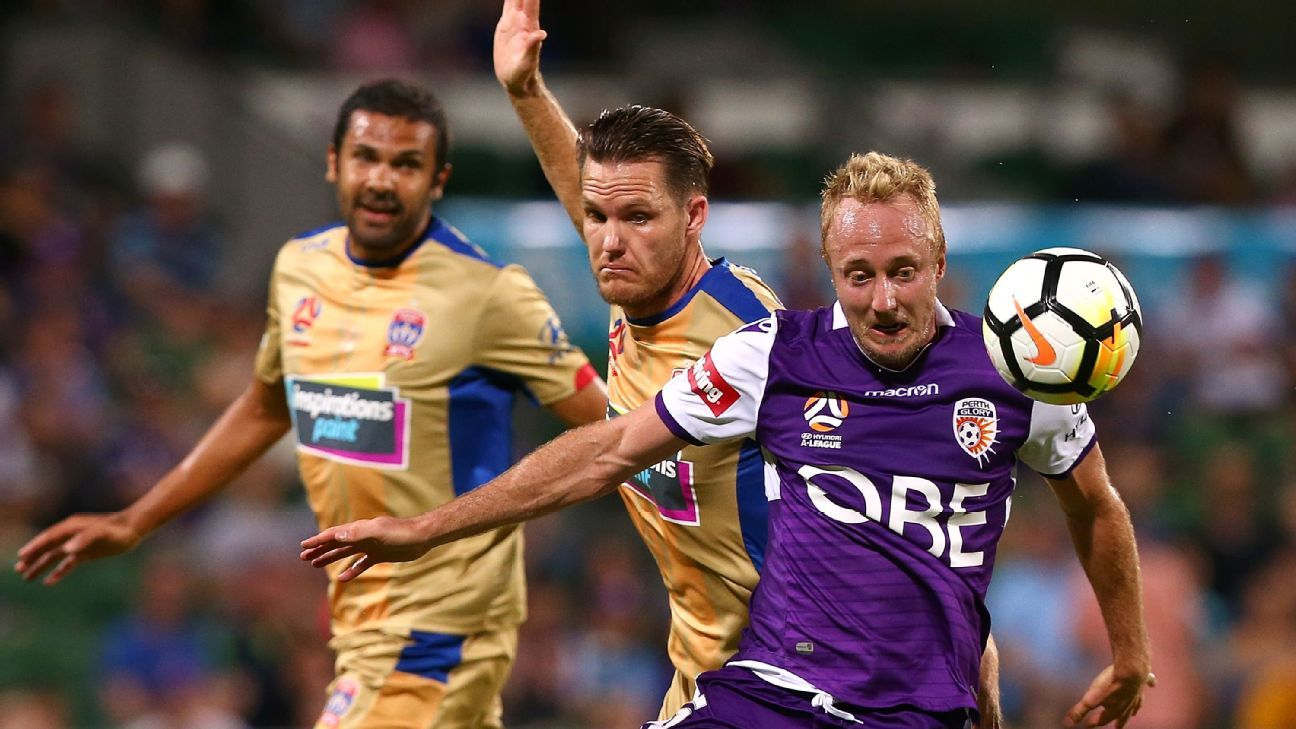 Mitch Nichols of Perth Glory controls the ball against Nigel Boogaard of Newcastle Jets during A-League match