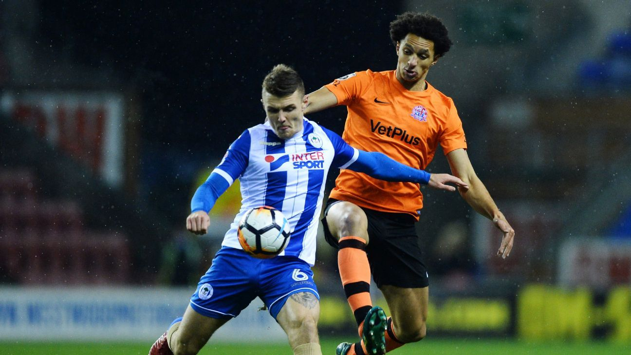 Lewis Montrose of AFC Fylde, right, and Max Power of Wigan Athletic battle for the ball in a FA Cup match.