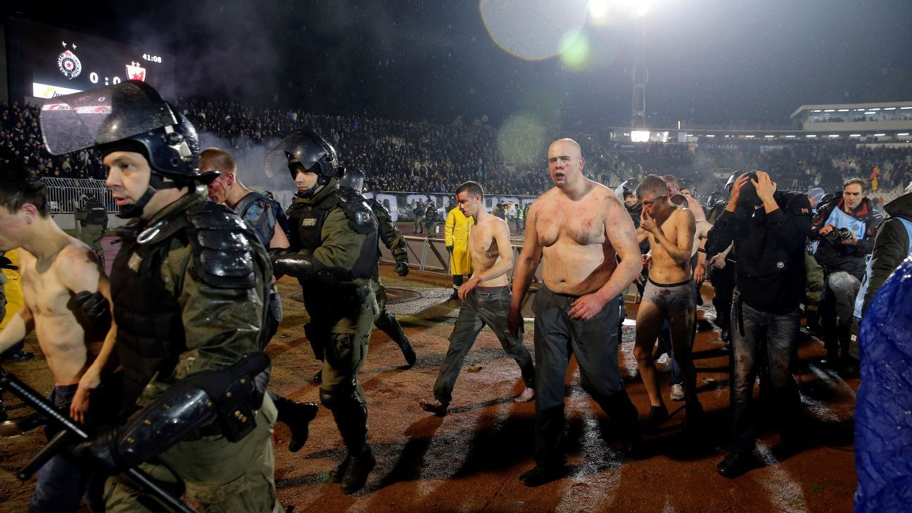 Belgrade police evacuated some supporters on to the pitch during the derby between Partizan and Red Star