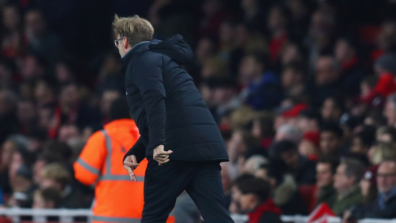 Jurgen Klopp throws a water bottle during Liverpool's Premier League game against Arsenal.