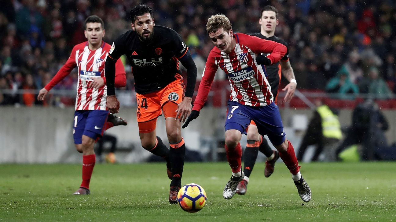Antoine Griezmann battles Ezequiel Garay of Valencia for the ball in a La Liga match.