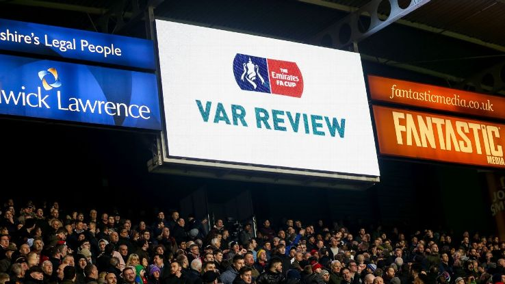 The big screen at Huddersfield shows that there is a VAR review being made.