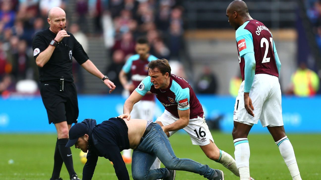 A pitch invader is tackled by West Ham's Mark Noble during the Premier League game against Burnley.