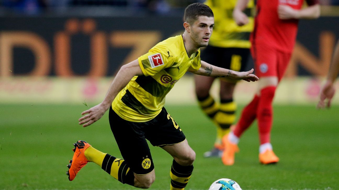 Dortmund's Christian Pulisic dribbles the ball between Eintracht Frankfurt defenders.