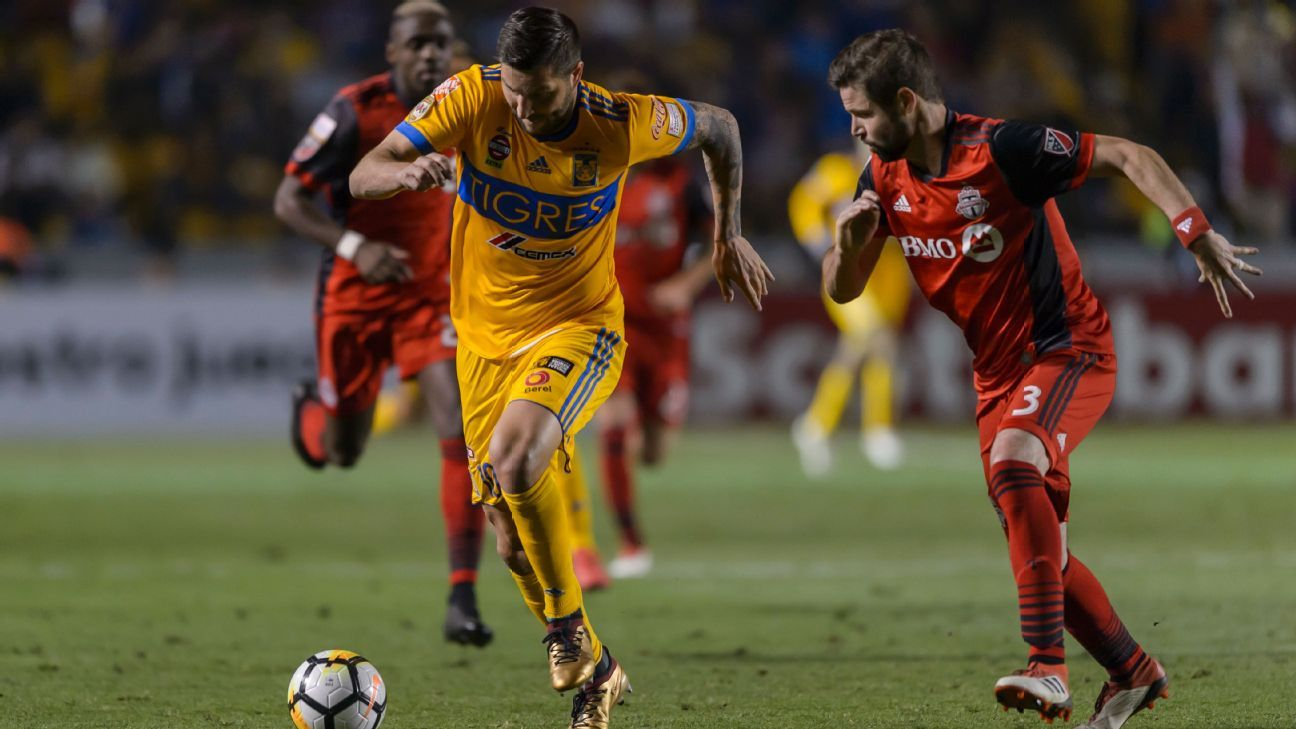 Andre-Pierre Gignac and Drew Moor battle for the ball in a CCL match between Tigres and Toronto FC.