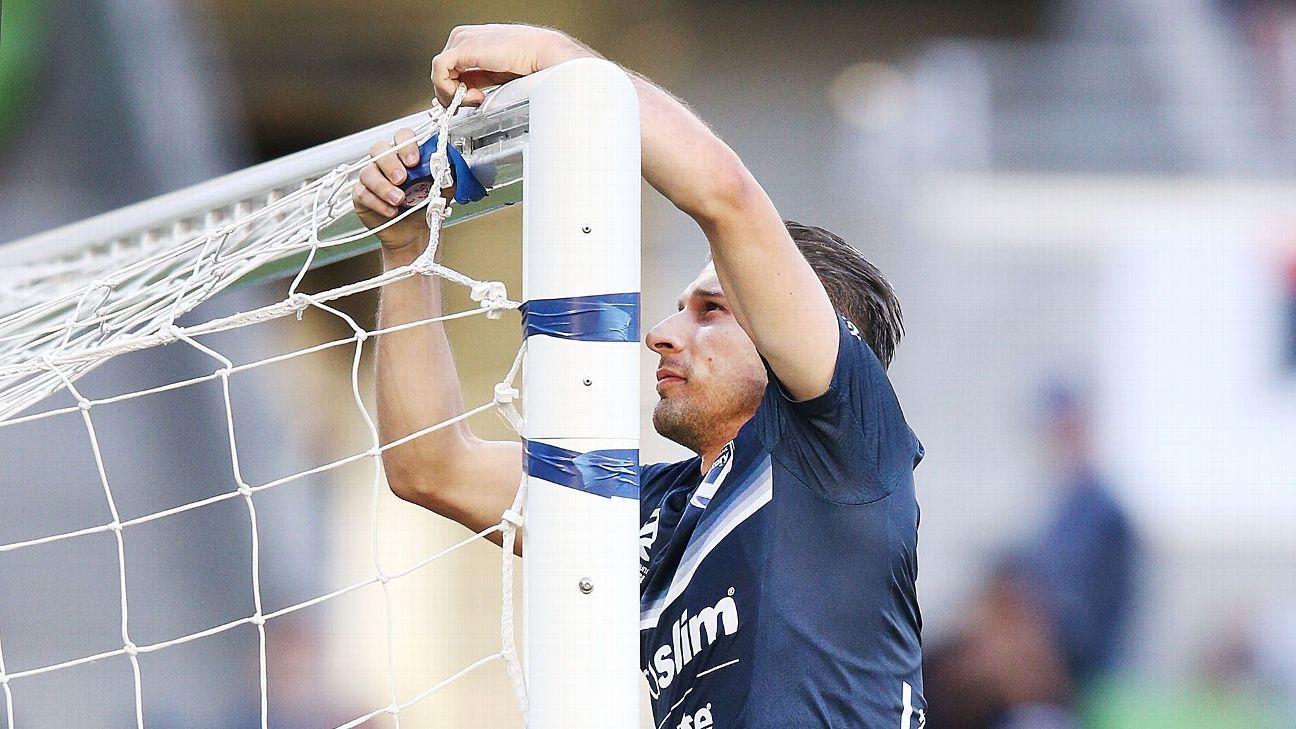 Melbourne Victory player Kostas Barbarouses repairs the broken net.