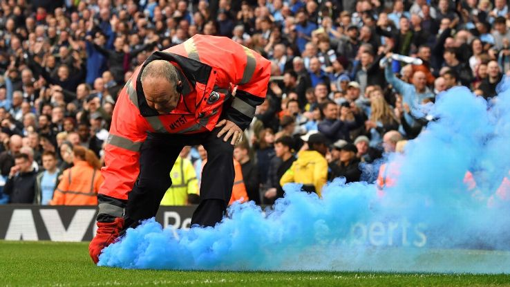A steward removes a blue flare from the pitch at the Etihad Stadium.