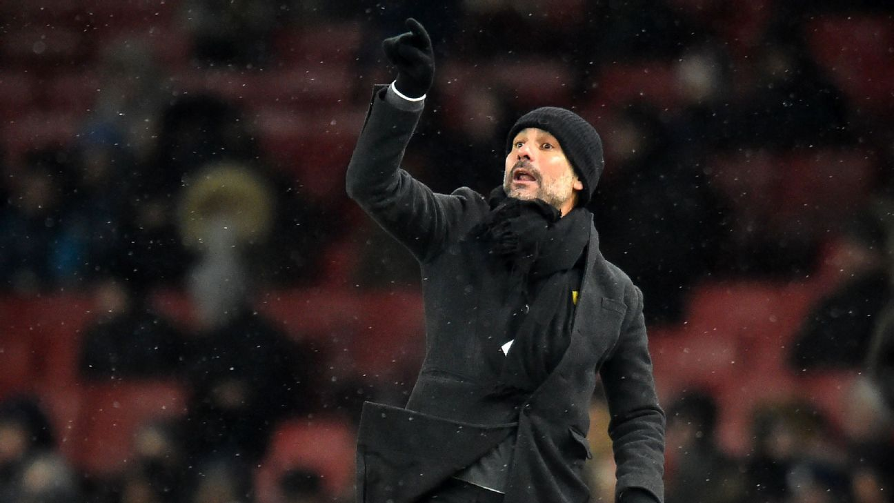Pep Guardiola gestures on the touchline as the snow falls