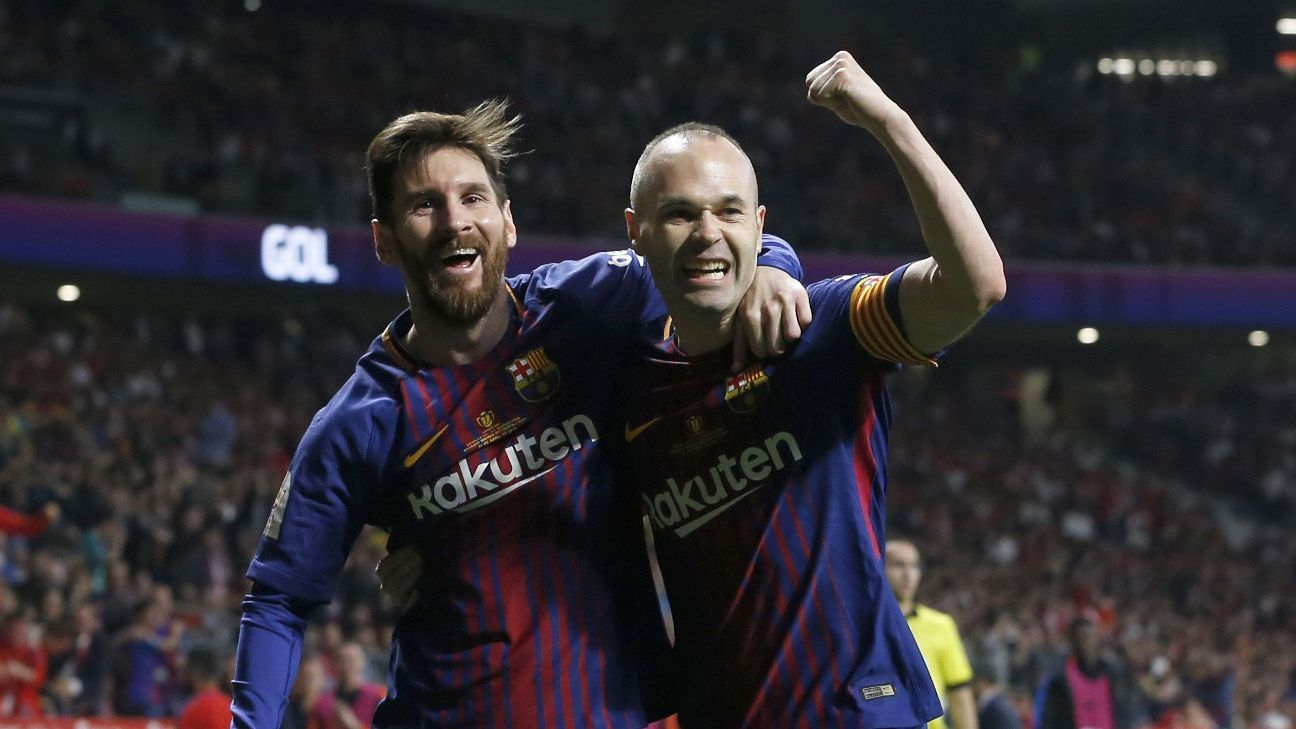 Andres Iniesta, right, celebrates with Lionel Messi after scoring vs. Sevilla.