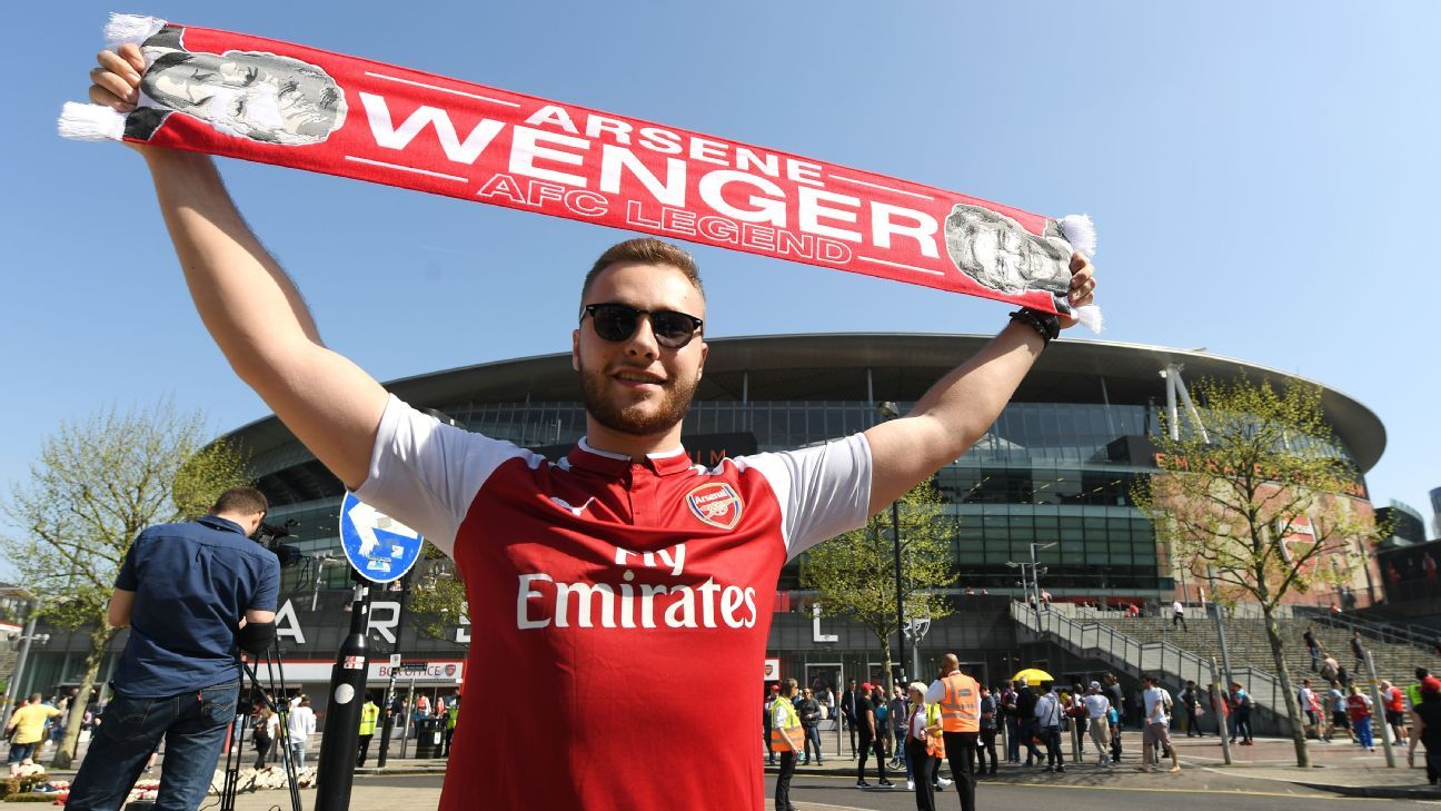 An Arsenal fan poses with an Arsene Wenger scarf prior to their Premier League match against West Ham United.