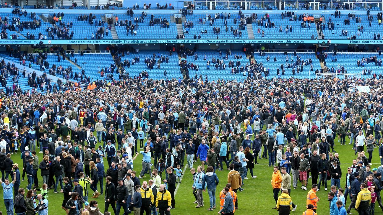 Manchester City fans invade the pitch following the Premier League win over Swansea.