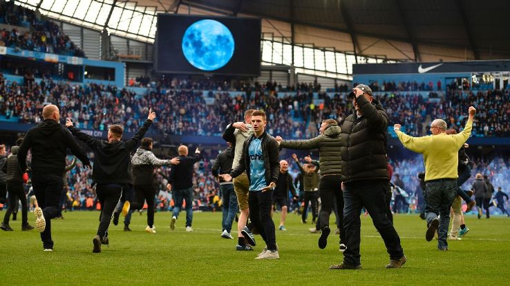 Manchester City fans invade the pitch following the 5-0 Premier League win against Swansea.