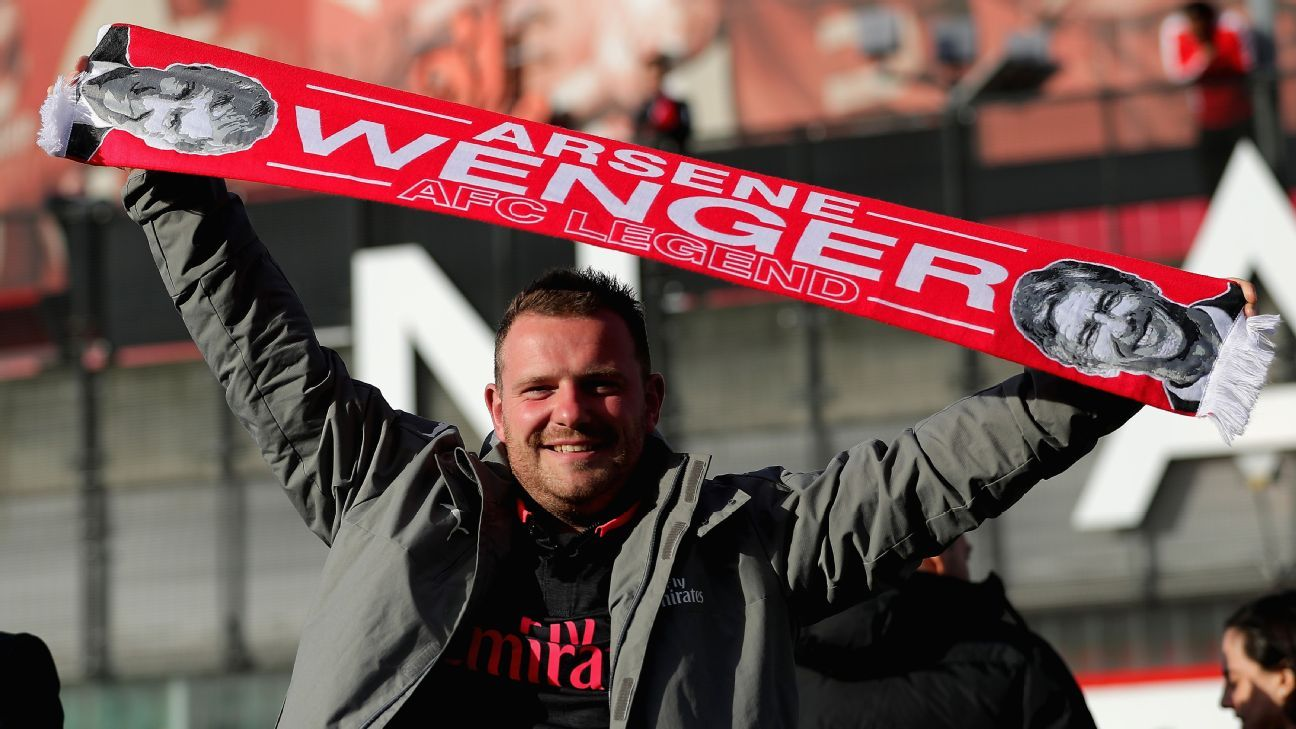 A supporter holds up an Arsene Wenger scarf prior to Arsenal's Europa League match vs. Atletico Madrid.