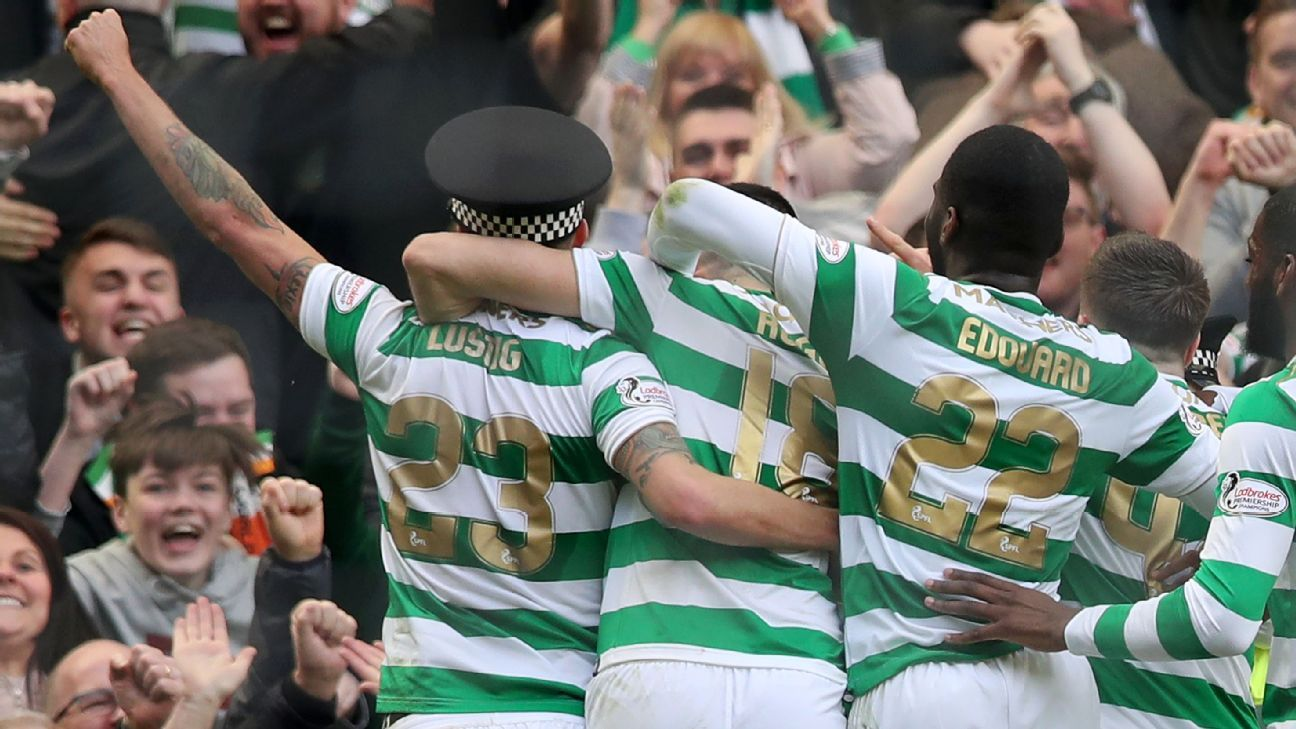 Celtic's Mikael Lustig celebrates his team's third goal vs Rangers by wearing policeman's hat