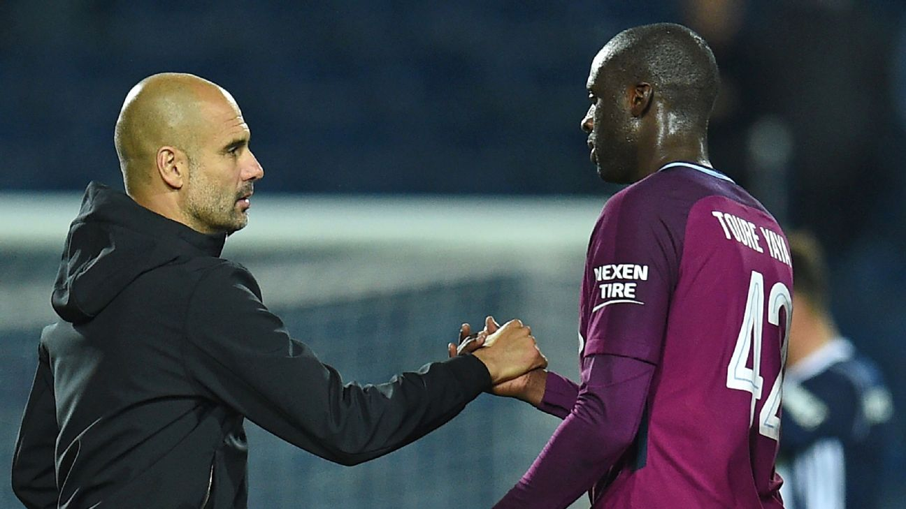 Manchester City manager Pep Guardiola, left, shakes hands with midfielder Yaya Toure