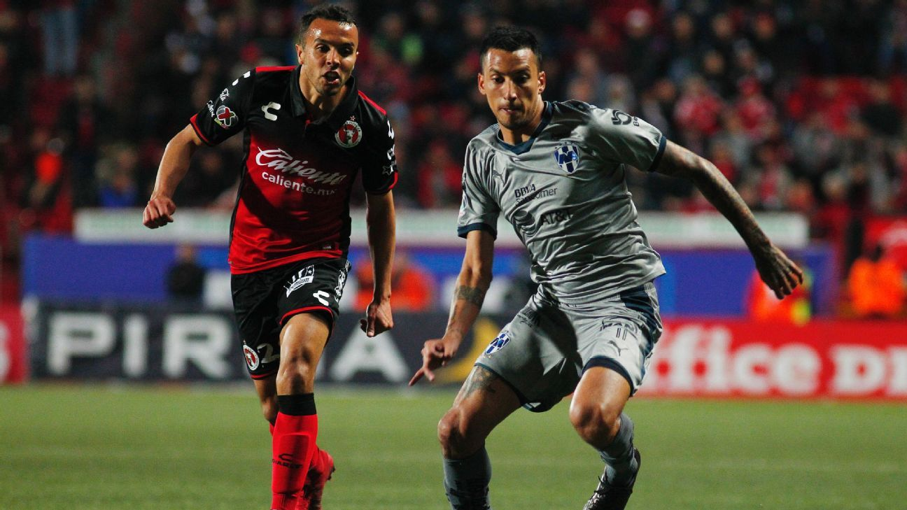Monterrey's Leonel Vangioni and Omar Mendoza of Tijuana vie for the ball during their Liguilla match.