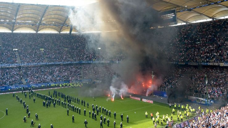 Fireworks burn and police guard the pitch as Hamburg's game against Borussia Monchengladbach was halted.
