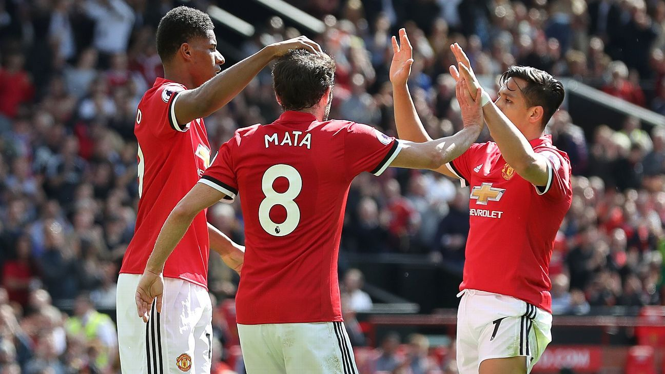 Manchester United's Marcus Rashford celebrates with teammates Juan Mata and Alexis Sanchez.