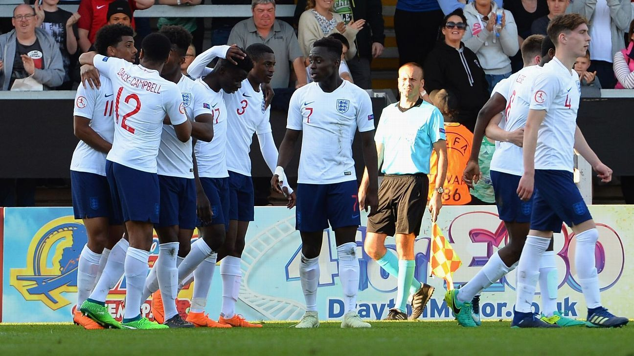 Xavier Amaechi is mobbed after scoring England's second goal.