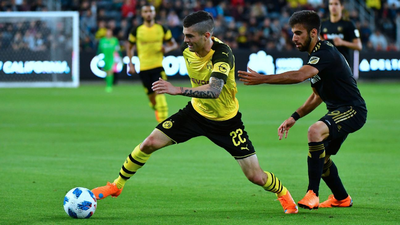 Borussia Dortmund's Christian Pulisic, left, evades LAFC's Diego Rossi in a club friendly at Banc of California Stadium.