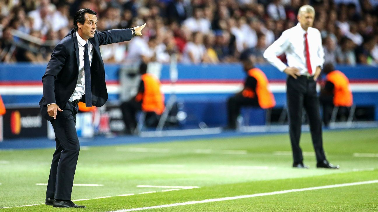 Unai Emery gestures while coach of Arsenal Arsene Wenger looks on.