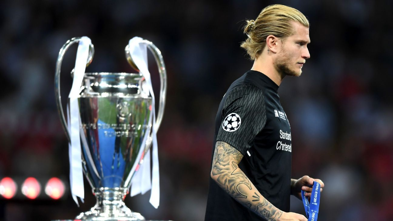 Loris Karius passes the Champions League trophy after Liverpool's 3-1 defeat against Real Madrid.