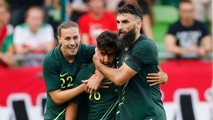 Australia's Mile Jedinak, left, celebrates with goalscorer Daniel Arzani and Jackson Irvine.