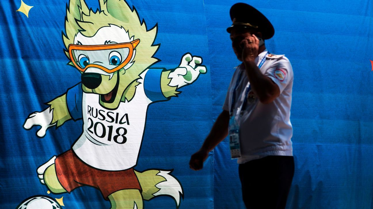A police officer speaks on a mobile phone in front of a banner featuring Zabivaka, the official World Cup mascot.