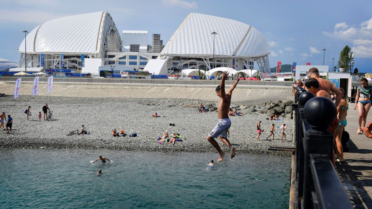 Young men jump off a breakwater in front of the Fisht Stadium, Sochi's World Cup venue.