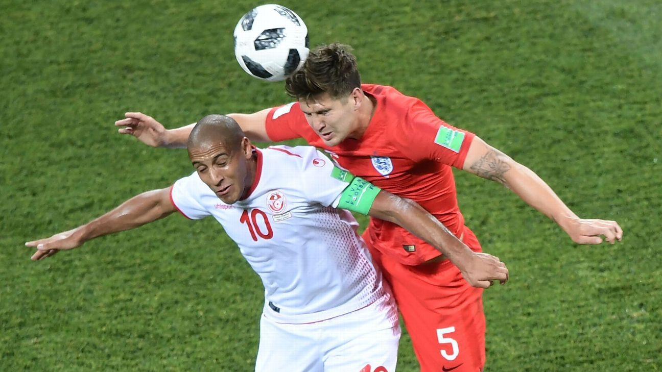 Wahbi Khazri (L) vies for the ball with England's defender John Stones.