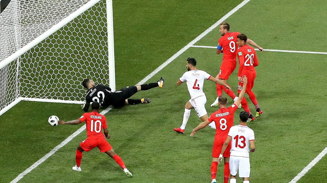 Harry Kane of England scores his team's first goal past Mouez Hassen of Tunisia.