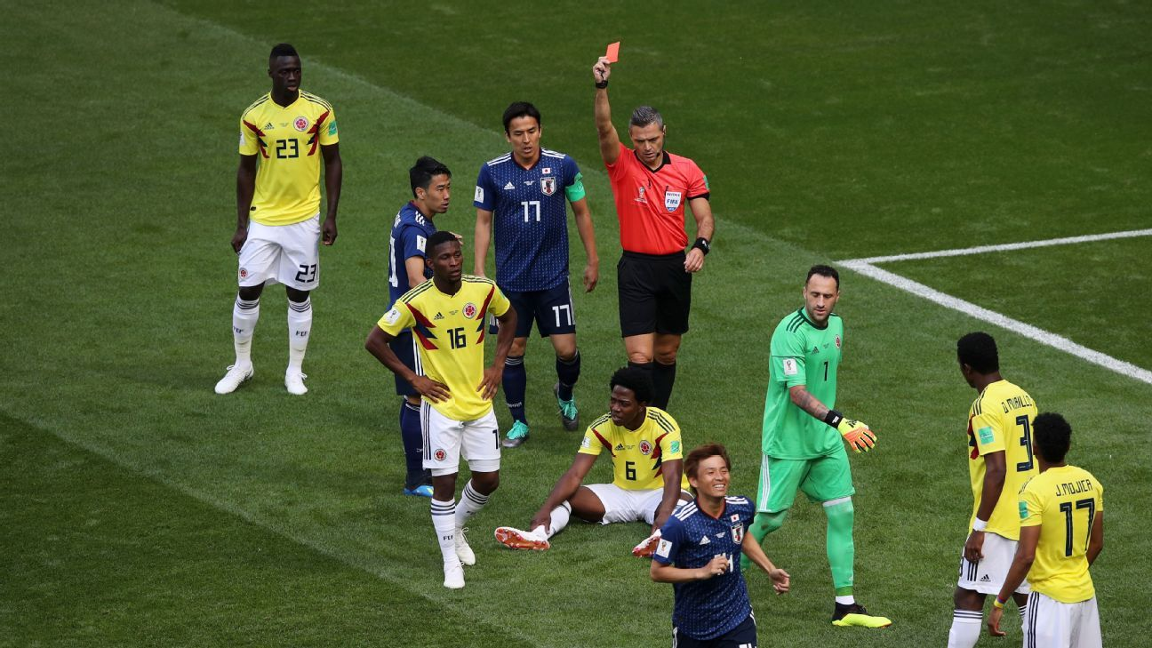 Carlos Sanchez (sat down) of Colombia is sent off by referee Damir Skomina.