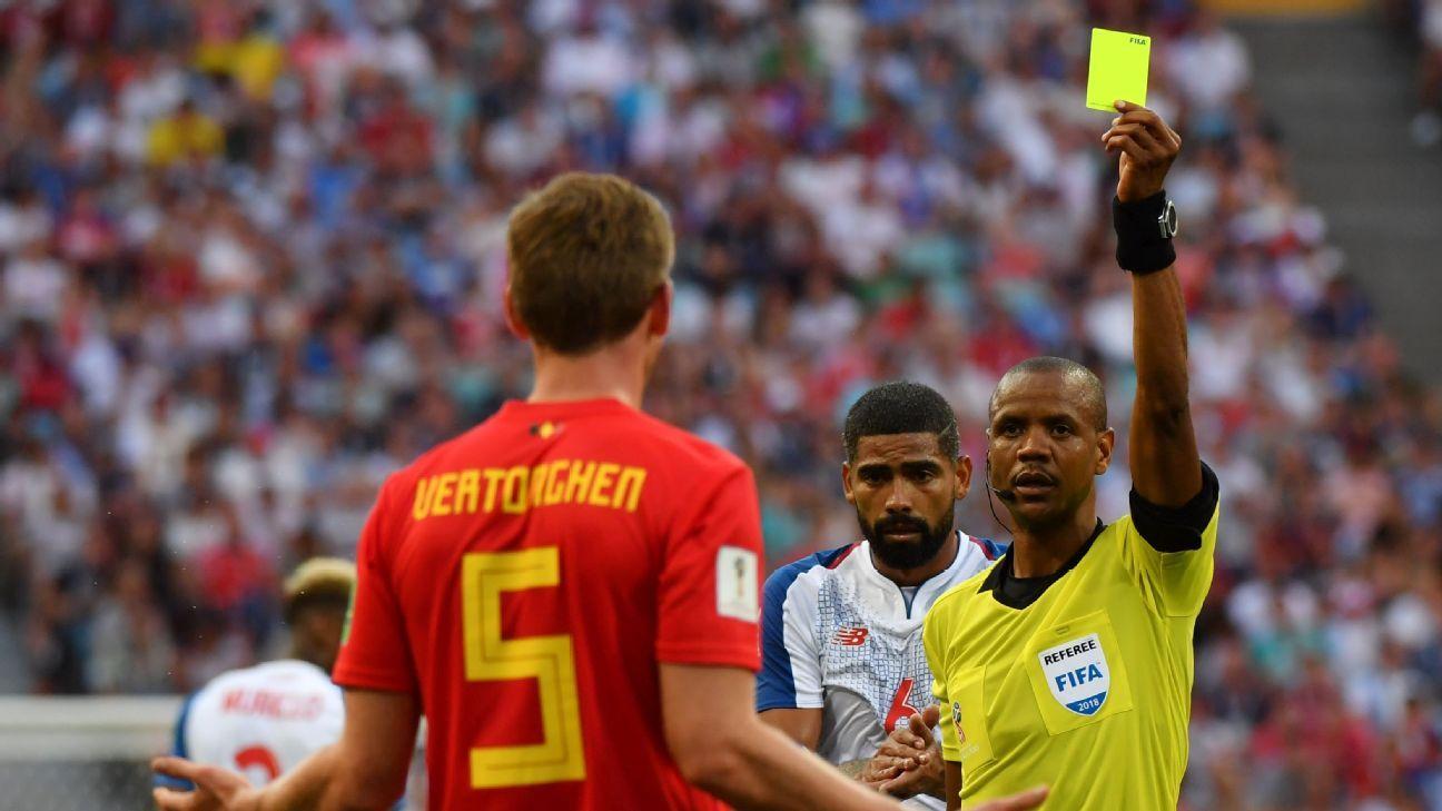 Referee Janny Sikazwe hands Belgium defender Jan Vertonghen a yellow card.