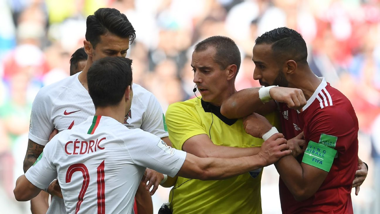 Referee Mark Geiger speaks with Morocco's Mehdi Benatia, right, and three Portugal players.