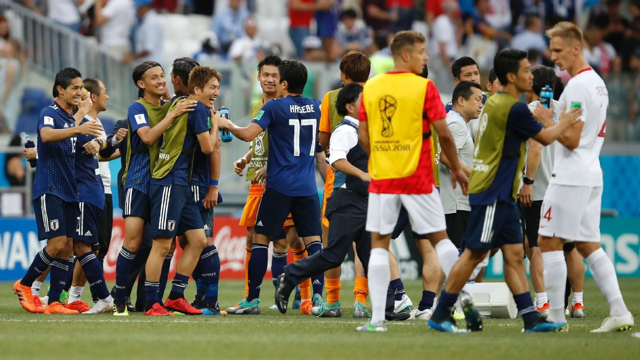 Japan celebrate qualifying for the round of 16 following a 1-0 defeat to Poland.