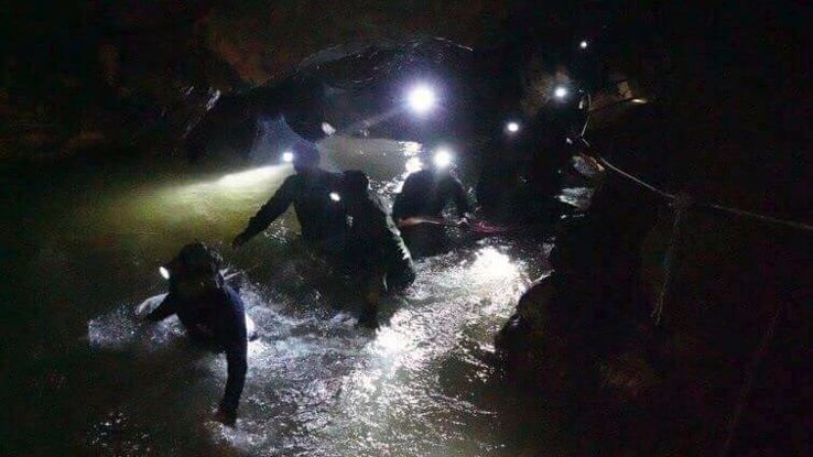 Thai rescue teams walk inside cave complex where 12 boys and their soccer coach went missing.