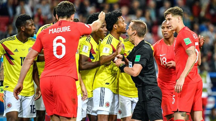 Referee Mark Geiger is surrounded by Colombia players.