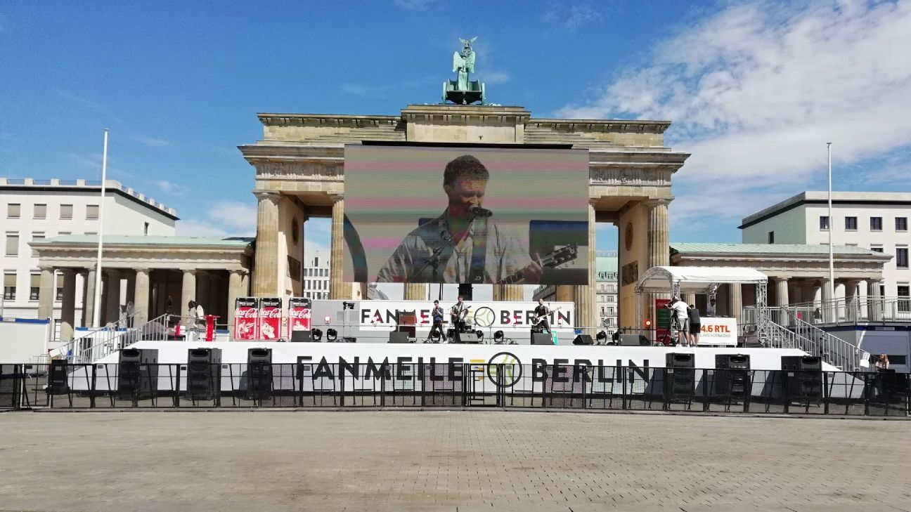 A band plays in front of an empty fan park at the Brandenburg Gate.