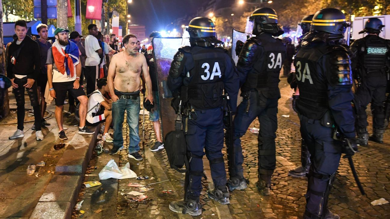 Police disperse people on the Champs Elysees in Paris after the World Cup final.