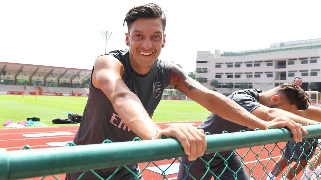 Mesut Ozil smiles as he takes part in Arsenal preseason training.