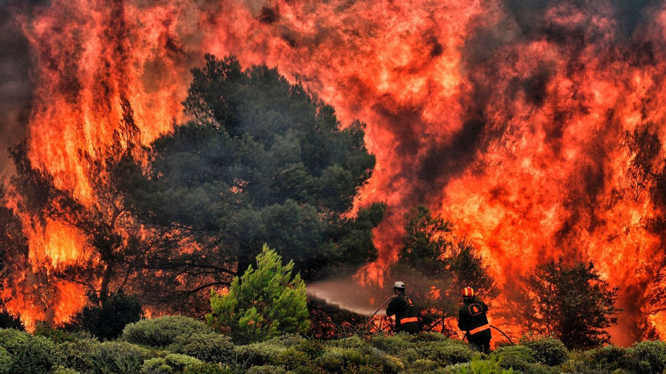 Firefighters try to extinguish flames during a wildfire near the village of Kineta, Greece.