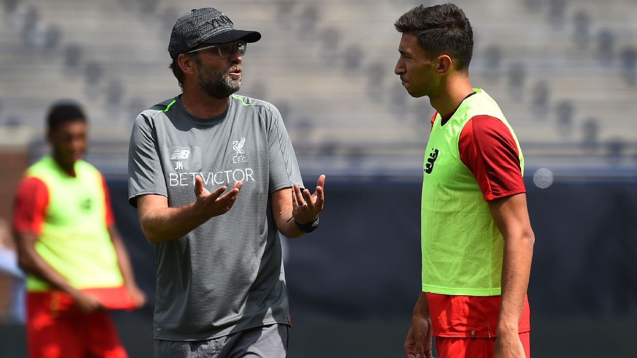 Jurgen Klopp and Marko Grujic talk during a Liverpool training session.